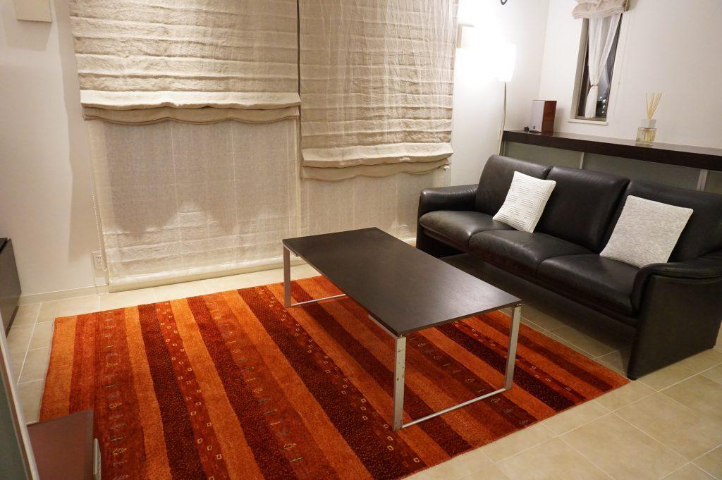 黒革のソファに赤色のギャッベ