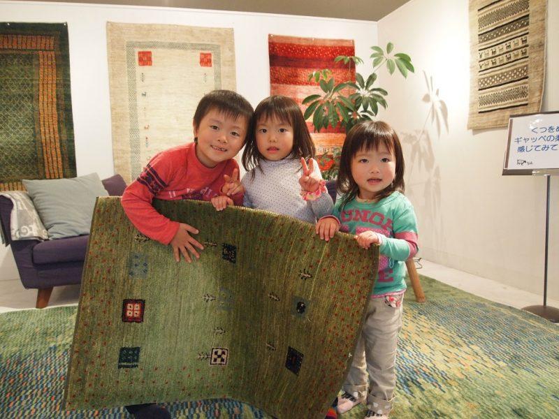 子ども達がギャッベを持っている。